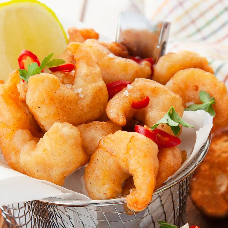 Golden Alehouse beer-batted shrimp, just deep-fried, in fryer in basket.