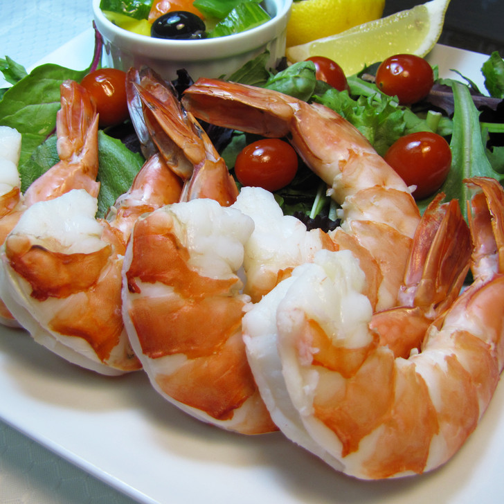 Giant shrimp arranged next to a salad with tomatoes.
