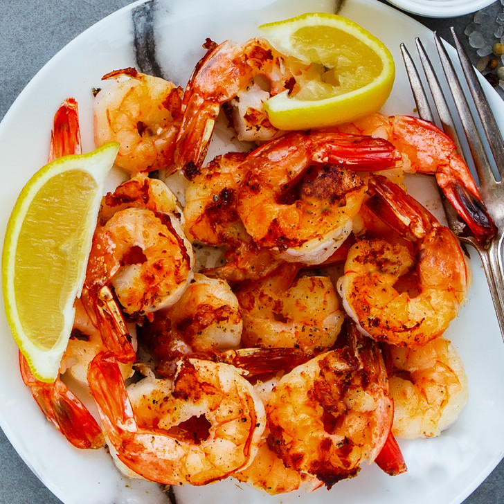 A savory plate of freshly grilled shrimp with lemon wedges.