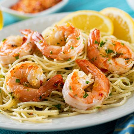 Spot shrimp scampi on a large bed of noodles with lemon slices.
