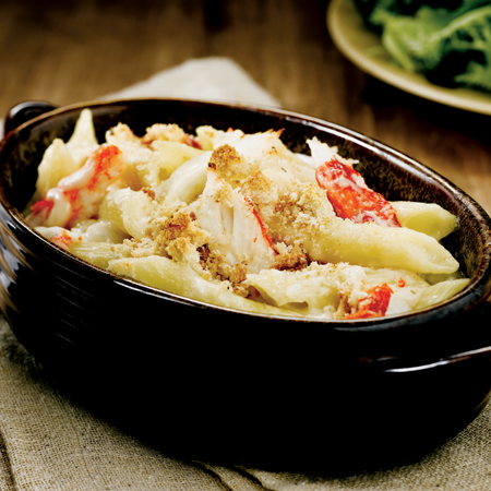 Ceramic dish filled with creamy king crab, penne pasta, and crispy breadcrumbs