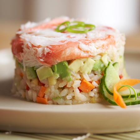 A snow crab sushi salad on a plate with garnish