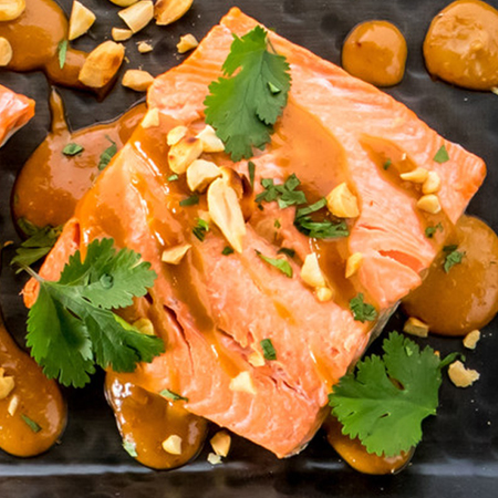Steamed salmon fillets topped with peanut sauce and cilanto
