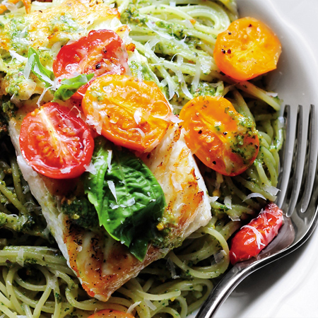 A freshly cooked halibut fillet atop a bed of pesto pasta with roasted tomatoes