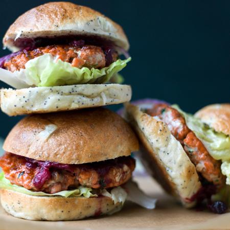 A stack of scrumptious sockeye salmon burgers with iceberg lettuce and rhubarb chutney
