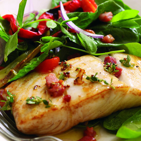 A broiled Alaska halibut fillet nestled in a festive pancetta salad