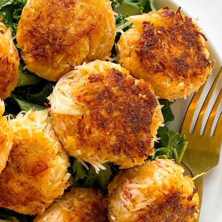A pile of crispy golden snow crab cakes on a bed of lettuce
