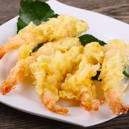 Crispy tempura battered shrimp on a square serving dish with leaf garnish