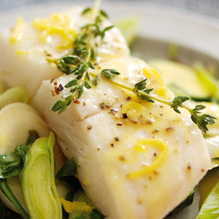 A cooked halibut fillet drizzled with lemon dressing on top of a bed of leeks & zucchini