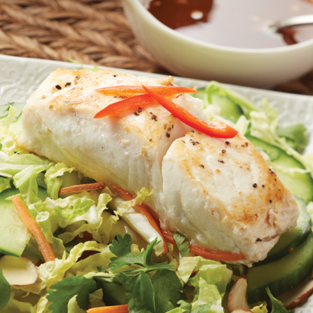 A cooked halibut fillet atop a healthy bed of salad