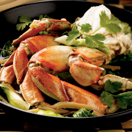 Dungeness crab legs in cooking pan with bok choy