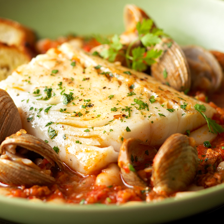 A black cod fillet and little neck clams in a spicy sauce