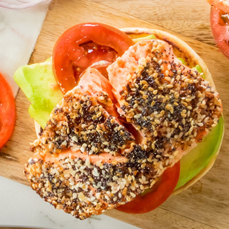 A spiced salmon fillet portion atop a toasted bagel with avocados and toppings