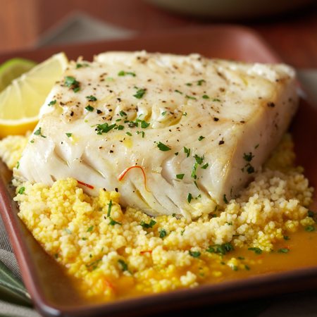 A poached fillet of black cod on a bed of couscous with lemon wedge