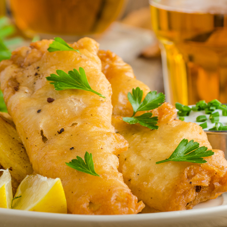 Two delicious beer battered fish fillets with fries, beer, & lemon wedges