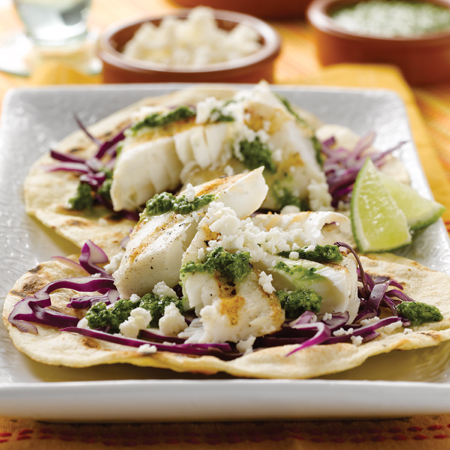 Charred tortillas with halibut & cilantro pesto on top sprinkled with cheese & cabbage shavings