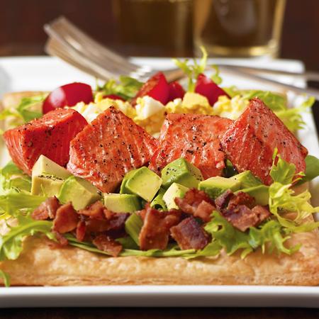 Roasted sockeye salmon on top a cobb salad on flat bread