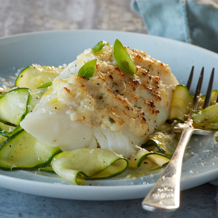 Broiled cod fillet with zucchini noodles topped with Parmesan cheese