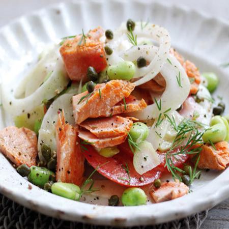 A healthy salmon, fennel, & tomato sadad in a shallow white bowl