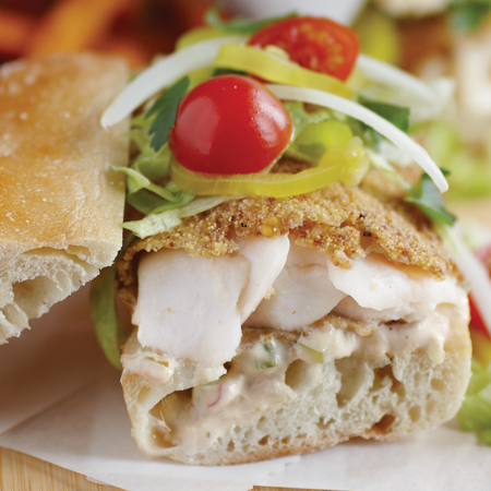 Crusted pan-fried cod portions within a hoagie roll sandwich