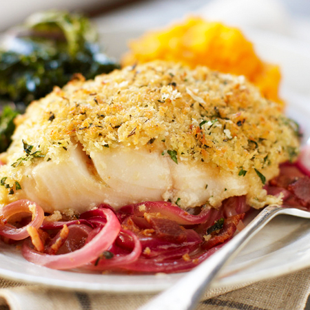 A herb-crusted fillet of black cod on a bed of braised red onions