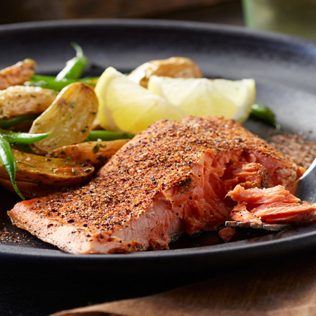 A broiled salmon fillet covered in spiced coffee rub with potatoes & green beans