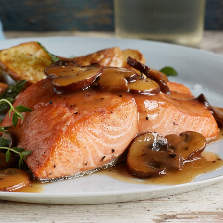 A cooked king salmon fillet covered with sliced mushrooms and sauce