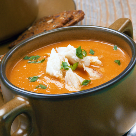 A two-handled soup cup fillet with hot crab bisque topped with crab chunks