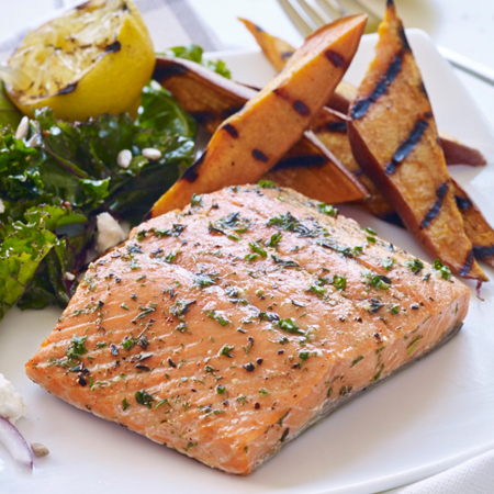 A cedar plank grilled salmon fillet with grilled sweet potatoes
