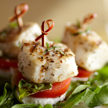 Skewered appetizers made with halibut, tomatoes, mozzarella cheese, & basil leaves