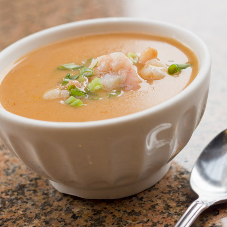 A bowl of creamy shrimp bisque garnished with peeled shrimp and scallions