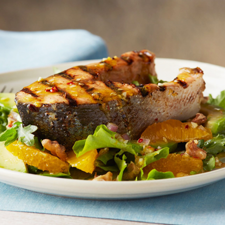 A thick grilled king salmon steak resting on top of an orange & avocado salad