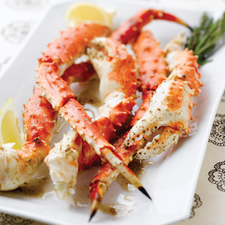 King crab legs & claws with lemon wedges on a long white platter