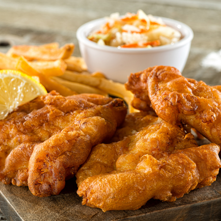 Several crunchy battered fish fillets with french fries, coleslaw and a lemon wedge