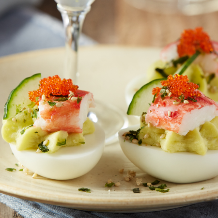 Deviled eggs filled with avocado mix and topped with king crab and Tobiko