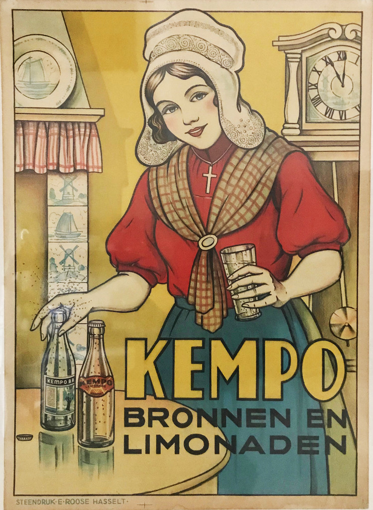 Kempo Bronnen En Limonaden 1920 Denmark - This Danish food poster features a woman in a red shirt and blue apron pouring a drink from two bottles on the table. Original Antique Posters.