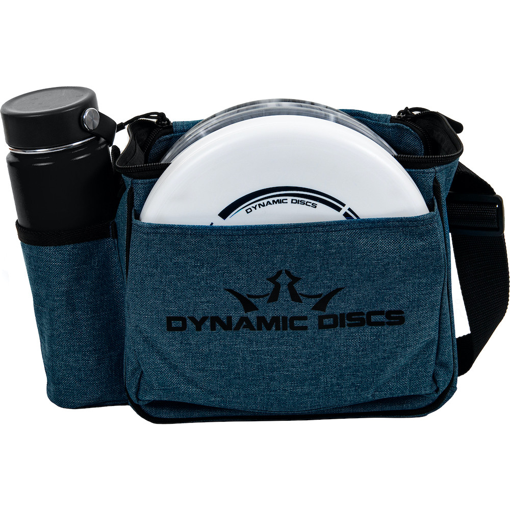 Front view of midnight blue Dynamic Discs Cadet starter bag. Shows water bottle in pocket on side to viewer's left, white disc in front pocket, and a single strap. Has black Dynamic Discs logo on front.