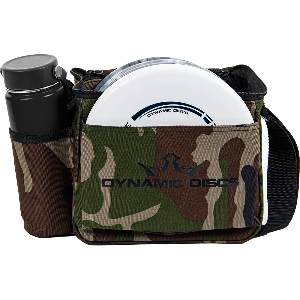 Front view of woodland camo Dynamic Discs Cadet starter bag. Shows water bottle in pocket on side to viewer's left, white disc in front pocket, and a single strap. Has black Dynamic Discs logo on front.