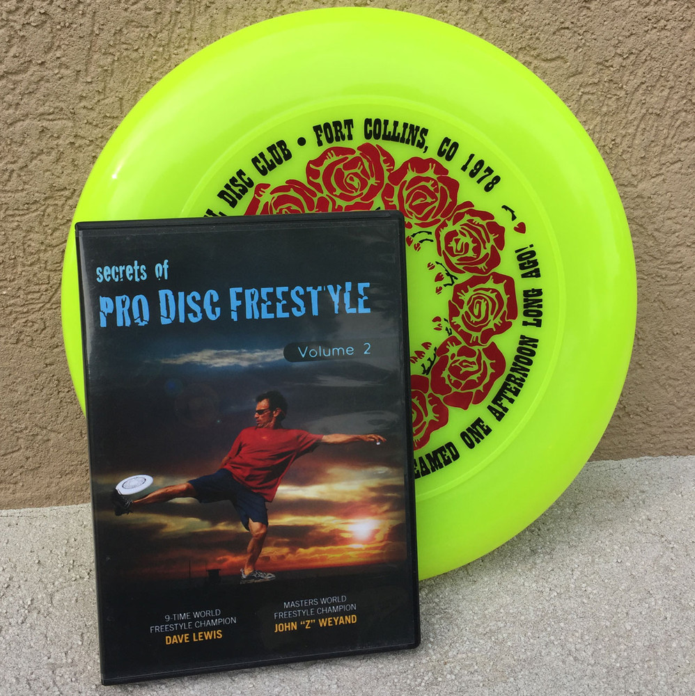 "Discraft SKY-STYLER + BONUS FREESTYLE DVD - Grateful Disc Roses Design  - shows yellow disc with a ""Secrets of Pro Disc Freestyle"" DVD both leaning up against a wall."
