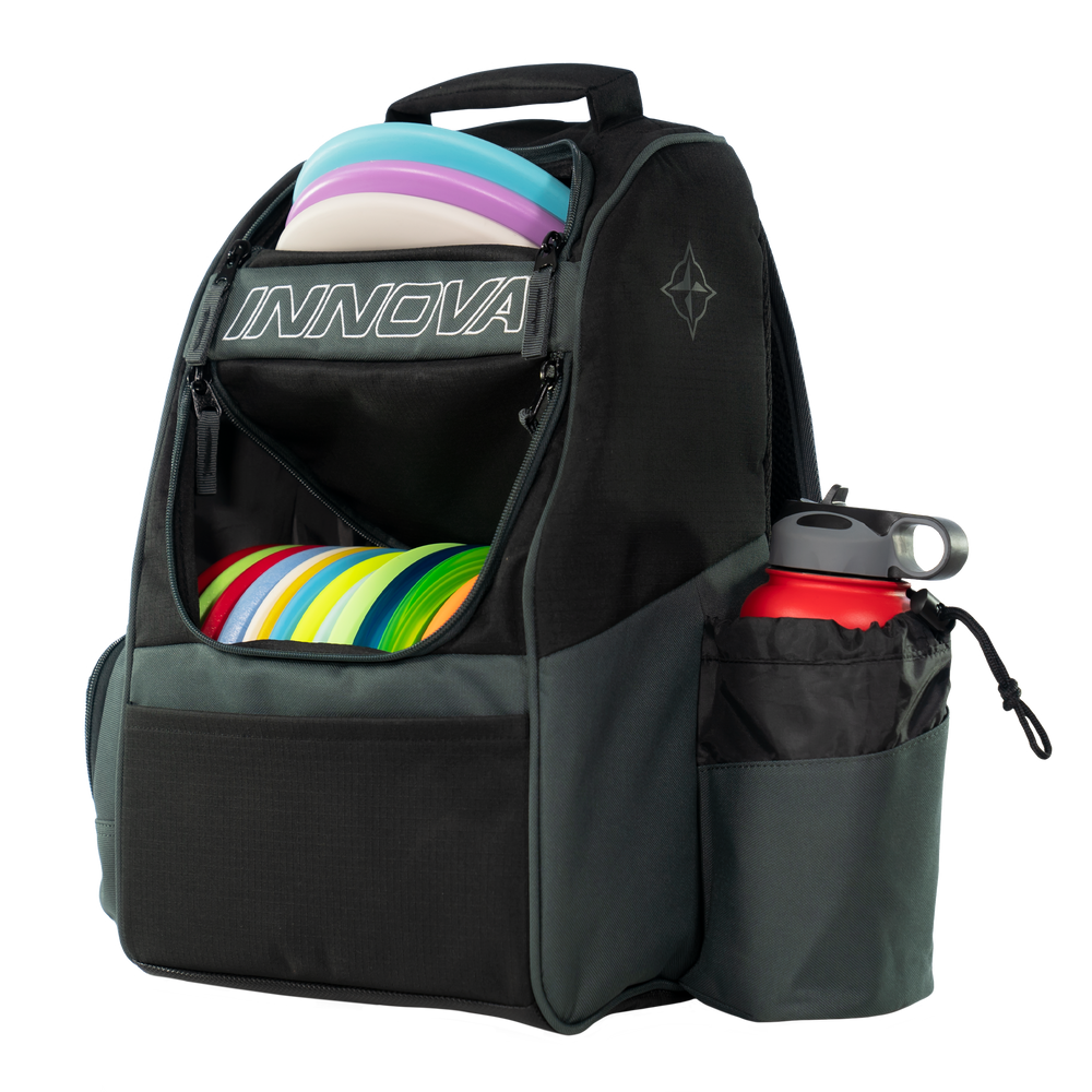Innova ADVENTURE BAG. Shows a black and gray bag pointing forward and to the viewer's left. It has the disc compartment open and is full of discs as well as a water bottle in its holder.