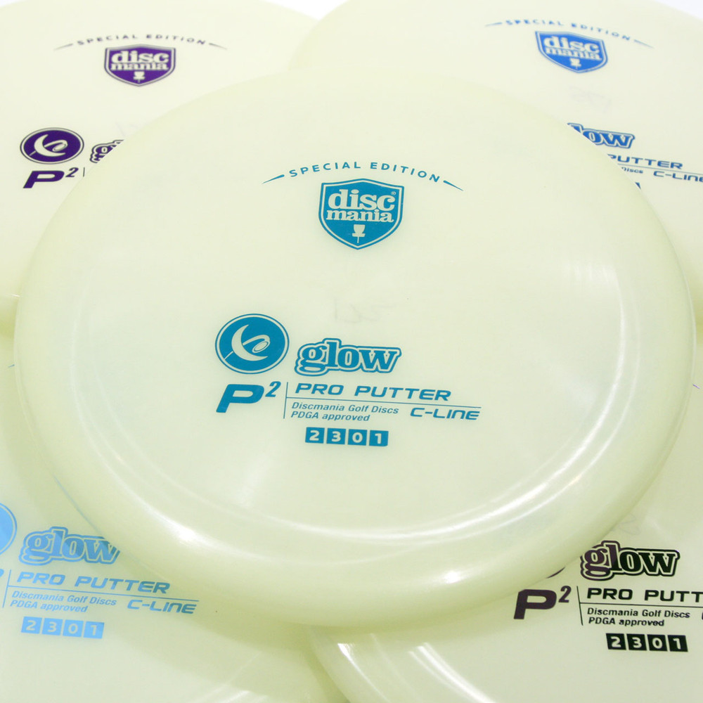 Discmania Glow C-Line P2. Shows angled top view of five white glow plastic discs with varying stamp colors spread out and overlapping. The disc centered in frame has a teal stamp.