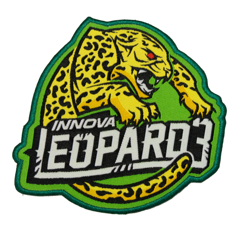 """Innova Leopard3 Patch. Shows a black-spotted yellow cat with red eyes and a fierce growl leaping over the words """"Innova Leopard3"""" on a green background."""