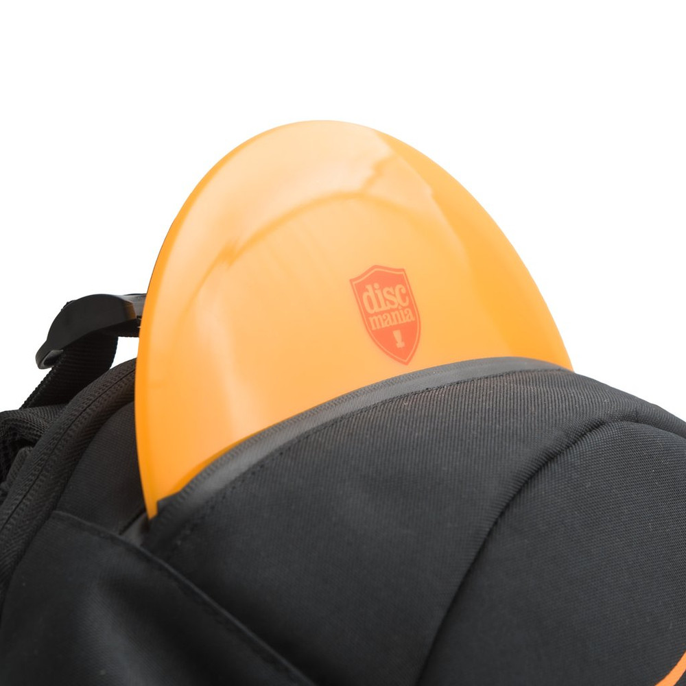 Shows a close up of an orange discmania disc sticking up parially out of the top pocket of a black Discmania Fanatic 2 Bag.