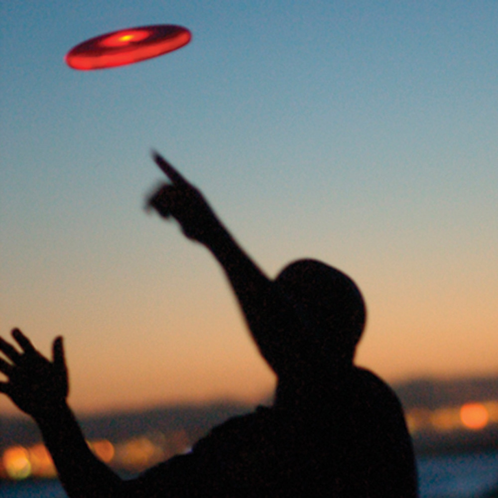Nite Ize FLASHFLIGHT - LED Light Up Flying Disc. Shows red disc glowing against a sunset sky and being caught by a silouette of the head and shoulders of a person.