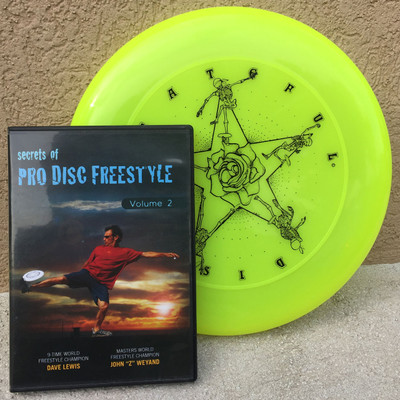 "Discraft SKY-STYLER + BONUS FREESTYLE DVD - Grateful Disc Design - shows yellow disc with a ""Secrets of Pro Disc Freestyle"" DVD both leaning up against a wall."