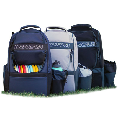 Innova ADVENTURE BAG. Shows three bags of different colors lined up and facing the viewer. The navy colored bag is in front and has the disc compartment open and full of discs as well as a water bottle in its holder.