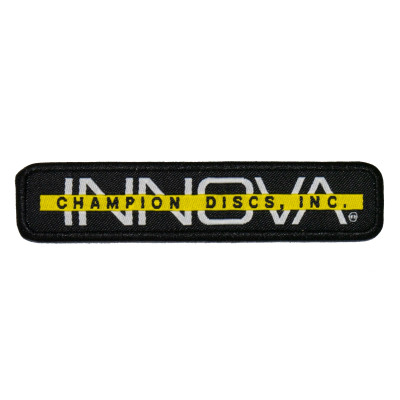 "Innova Bar Stamp Patch. Shows a long rectangular patch with black background. The word INNOVA is white and capitalized, and a yellow bar goes across center of the letters. The bar has ""Champion Discs"" written in black."