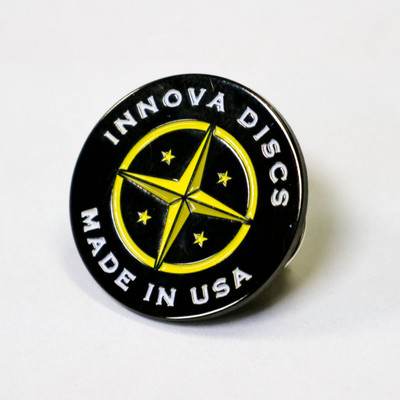 """Shows the Innova Proto Star Lapel Pin Button against a white background. The colors are black background with white for """"Innova Discs, Made In USA"""" and yellow for the star and circle graphic."""