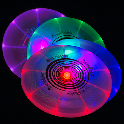 Nite Ize FLASHFLIGHT - LED Light Up Flying Disc. Four different colors of discs are shown glowing in the dark, leaning against each other.