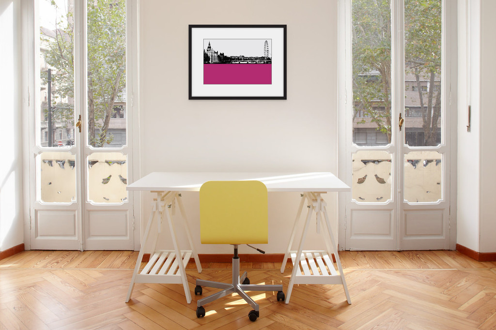 Art print of the London Eye and Westminster by designer Jacky Al-Samarraie, mounted and framed on a wall in an office room.  The print colour is pink.